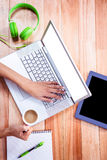 Overhead of feminine hands using laptop and holding coffee Royalty Free Stock Photography