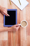 Overhead of feminine hands using tablet and holding coffee Stock Photography