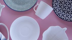Overhead flat lay view of white tableware on pink background. Overhead flat lay view of white clean tableware on pink background stock video