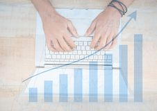 Overhead of hands on laptop with blue graph overlay Stock Photo