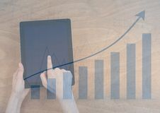 Overhead of hands with tablet and blue graph overlay Stock Photos