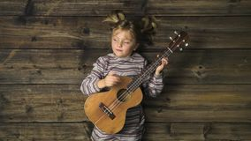 Overhead happy child girl on vintage wooden background playing ukulele guitar.Text or logo copy space.Vertical top view. Social card for Christmas holiday stock footage