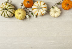 Overhead, horizontal flat lay still life of assorted orange and white pumpkins and ornamental squash on white wood background