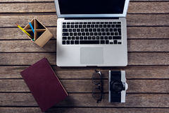 Laptop, diary, spectacles, camera and pen holder on wooden table. Overhead of laptop, diary, spectacles, camera and pen holder on wooden table Royalty Free Stock Photo