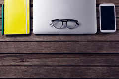 Laptop, diary, spectacles and mobile phone on wooden table. Overhead of laptop, diary, spectacles and mobile phone on wooden table Royalty Free Stock Photo