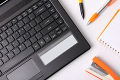 Overhead of laptop and office supplies. Overhead shot of a laptop and some office supplies laid on top of white table stock photo