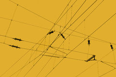 Overhead Lines. Used to transmit electrical energy to trams, trolleybuses or trains over a yellow background Royalty Free Stock Photography