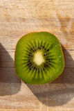 Overhead macro shot of the kiwi slice on a wooden board Stock Photography