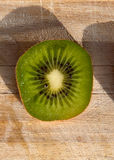Single kiwi slice on a wooden board Stock Photography