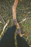 Overhead of man boots treading a pine log. Royalty Free Stock Photos
