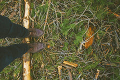 Overhead of man boots treading a pine log. Royalty Free Stock Photo