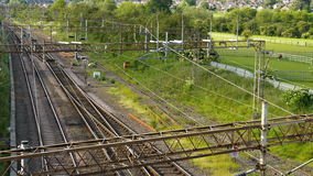 Overhead Metal high voltage electric supply cables over UK railway stock footage