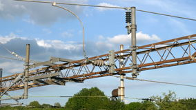 Overhead metal high voltage electric supply cables over UK railway stock video