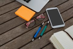 Mobile phone, laptop, pen, sticky note, spectacles and organizer on wooden plank. Overhead of mobile phone, laptop, pen, sticky note, spectacles and organizer on Stock Photography