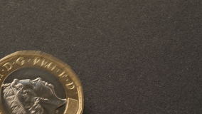 Overhead new uk one pound coin spinning stock video footage