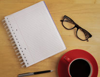 Overhead of notebook and glasses with pen and coffee cup Stock Photo