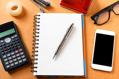 Overhead of office table with notebook, pen, mobile phone , calc. Ulator, eye glasses and office supplies, gadgets in modern office with accessories - top view Stock Photography