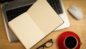 Overhead of open notebook on laptop. On a desk Royalty Free Stock Image