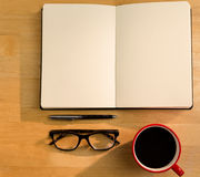 Overhead of open notebook with pen glasses and coffee Stock Photography