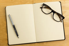 Overhead of open notebook with pen and glasses Stock Images