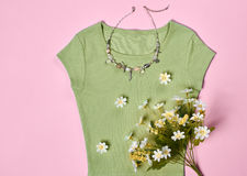 Overhead outfit fashion essentials set, flowers. Overhead outfit Fashion Ladies, accessories. Glamor creative  T-shirt, flowers, necklace, bouquet of camomile Royalty Free Stock Photos