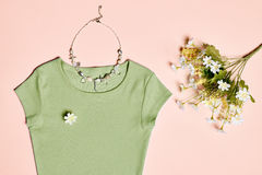 Overhead outfit fashion essentials set, flowers. Overhead outfit Fashion Ladies, accessories. Glamor creative  T-shirt, flowers, necklace, bouquet of camomile Stock Photo