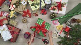 Overhead person hands preparing gift present finishing ribbon.Vertical top view of wooden table full of christmas gift. Boxes.Xmas holiday season social card stock video footage
