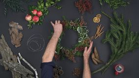 Overhead person hands preparing wreath garland.Vertical top view of dark table with natural leaves,pine cones,bark. Cinnamon, oranges, pomegranate.Xmas holiday stock footage