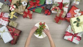 Overhead person hands putting gift present and greetings card on text or logo copy space.Vertical top view of wooden. Table full of christmas gift boxes.Xmas stock footage