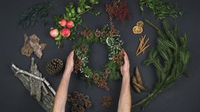 Overhead person hands putting wreath garland on text copy space.Vertical top view of dark table with natural leaves,pine. Cones,bark, pomegranate.Xmas holiday stock video footage