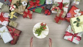 Overhead person hands taking the main gift present leaving text or logo copy space.Vertical top view of wooden table. Full of christmas gift boxes.Xmas holiday stock footage