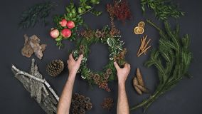 Overhead person hands taking wreath garland on text copy space.Vertical top view of dark table with natural leaves,pine. Cones,bark, pomegranate.Xmas holiday stock video footage