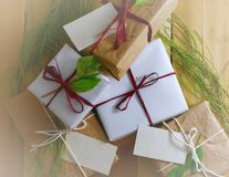Overhead perspective of a collection of gifts wrapped in natural white and brown papers tied with jute and string. Some of the pre. Sents have name tags. Cypress stock images