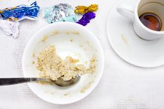 An overhead photo of dirty plate with porridge leftovers, chocolate candies wrapper, spoon and a cup of black espresso coffe. Royalty Free Stock Image