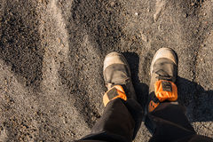 Overhead photo of feet on a background of brown sand. Man feets. Royalty Free Stock Images