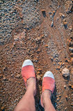 Overhead photo of feet on a background of brown sand. Women feets view from above. Exploring, travelling, tourism, leisure. Stock Photography