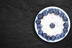 An overhead photo of fresh natural cottage cheese with blueberries in a blue ceramic bowl on the black stone plate. Organic eco stock photo