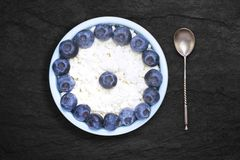 An overhead photo of fresh natural cottage cheese with blueberries and a silver spoon in a ceramic bowl on the black stone desk. royalty free stock photos