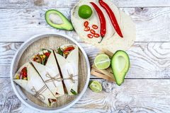 An overhead photo of Mexican burritos with beef, avocado beans, and vegetables, with a cheese sauce, chili peppers on wooden royalty free stock images