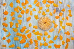An overhead photo of tangerine without peel. Peeled juicy tangerine on the wooden blue table and pieces of peel. An overhead photo of tangerine without peel Royalty Free Stock Photography