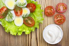 An overhead photo of vegetable salad with mayonnaise, boiled quail eggs, dill, fresh tomato and lettuce. A served salad photo from stock photos
