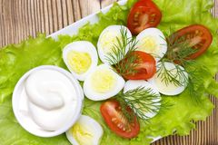 An overhead photo of vegetable salad with mayonnaise, boiled quail eggs, dill, fresh tomato and lettuce. A served salad photo from royalty free stock photo