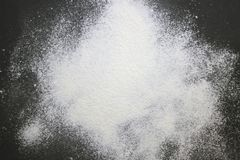 An overhead photo of wheat white flour sprinkled on the black wooden table. Top view, place for text. Flour ready to knead the dou Stock Images