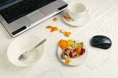 Overhead photo of workplace after breakfast. A cup of coffee with laptop on tablecloth, empty bowl with porridge leftovers, half o. Overhead photo of workplace Stock Image