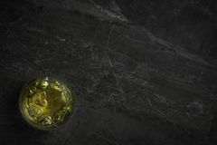 An overhead photograph of a glass of golden Whiskey with ice on a dark marble rock background stock photos