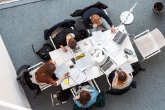 Overhead picture of students studying in coworking space. Vilnius Lithuania - April 23 2016: Overhead high angle picture of young male students sitting and Stock Images