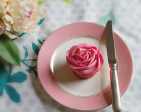 Overhead of pink rose frosted cupcake on vintage plate Royalty Free Stock Image