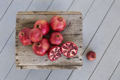 Overhead of Pomegranates on weathered wood. Overhead view of freshly picked pomegranates displayed on  weathered wood table on grey porch wood flooring Stock Image
