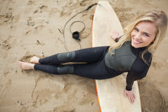 Overhead portrait of blond in wet suit with surfboard at beach Stock Photo