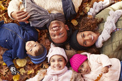 Overhead Portrait Of Family Lying In Autumn Leaves royalty free stock photography
